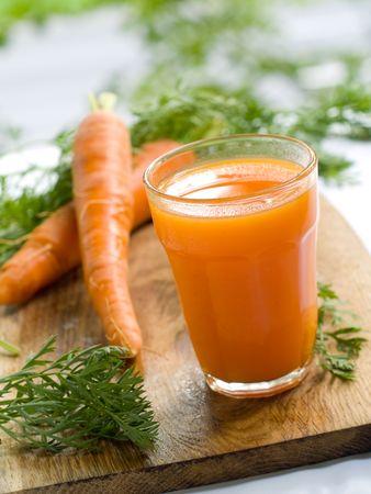 zanahoria: vaso de zumo de zanahoria fresca y algunas hortalizas frescas  Foto de archivo