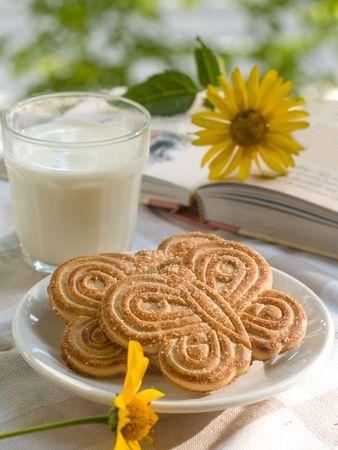Glas melk met twee cookies. Boek met bloem op achtergrond