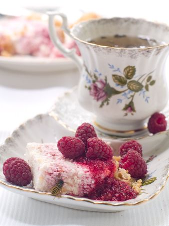 cheesecake  with raspberry on plate and cup of tea photo