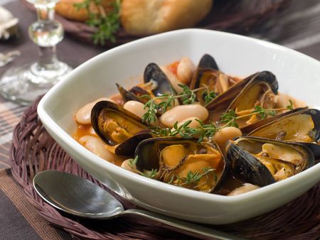 mussel: mussel soup with bean and thyme on bowl