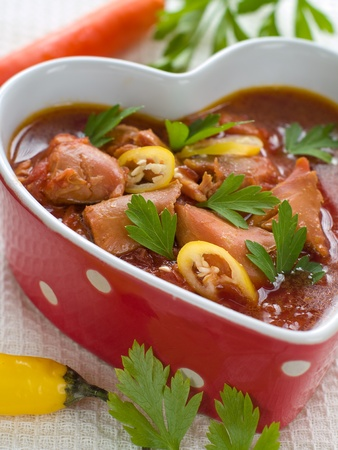 Healthy beef stew in heart shaped bowl  with parsley and chili photo