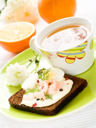 Sandwich with cheese and shrimp and cup of tea for breakfast photo