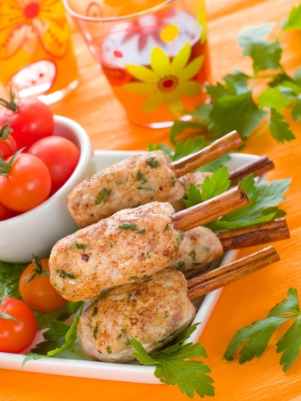 pork (or chicken) kebab on cinnamon stickst with salad and tomatoes Stock Photo