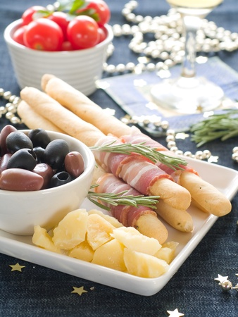 Sumptious platter served with olives, cheese and ham on bread sticks. Shallow DOF.  photo