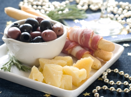 sumptious: Sumptious platter served with olives, cheese and ham on bread sticks. Shallow DOF.  Stock Photo