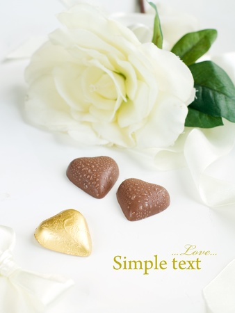 Three chocolate hearts with white flower on background photo
