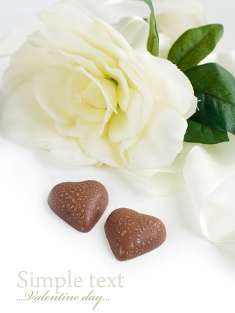 Two chocolate hearts with white flower on background photo