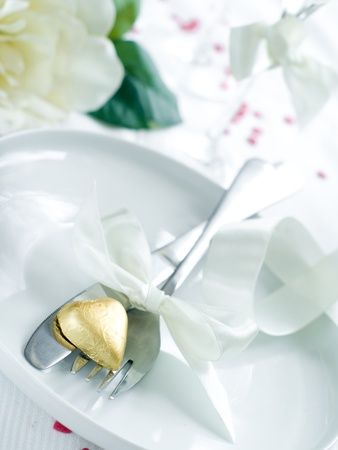Fork and knife laying on plate with ribbon and heart Stock Photo - 8657452