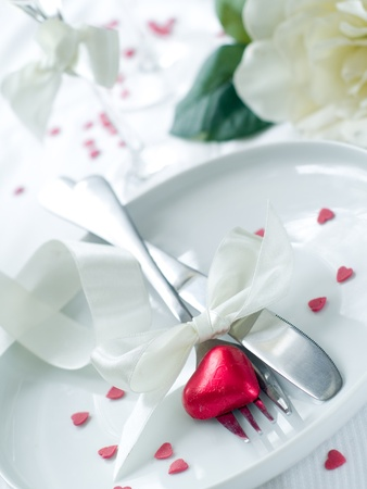 Fork and knife laying on plate with ribbon and heart Stock Photo - 8657453