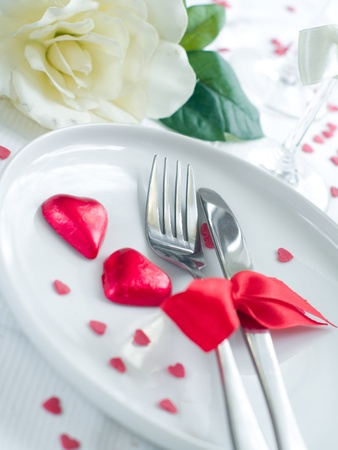 Fork and knife laying on plate with ribbon and heart Stock Photo - 8657456
