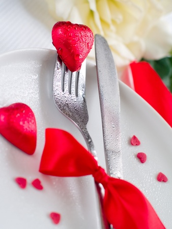Fork and knife laying on plate with ribbon and heart Stock Photo - 8657475