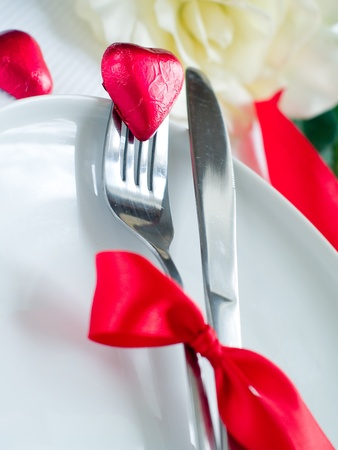 Fork and knife laying on plate with ribbon and heart Stock Photo - 8657465