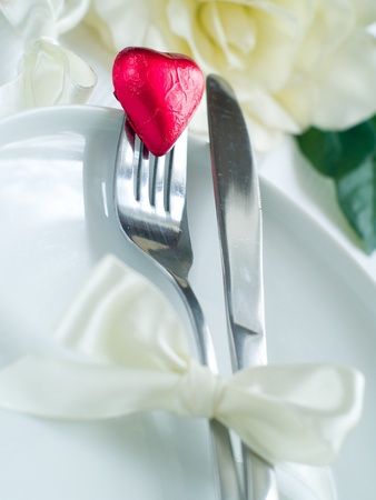 Fork and knife laying on plate with ribbon and heart Stock Photo - 8657457