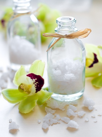 Jar of sea salt and flower on wood photo
