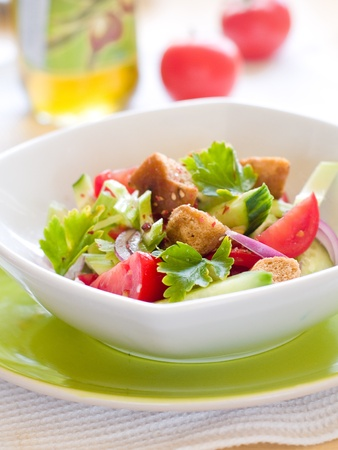 Fresh salad with onions, tomatoes, cucumbers and croutons  photo