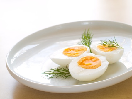 yolk: Cooked egg  on white plate with dill Stock Photo
