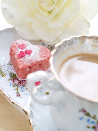Cup of tea with milk served with strawberry cake. Selective focus photo