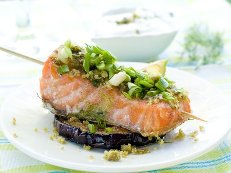 A grilled salmon fillet with grilled eggplant and wine photo