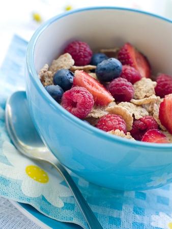 comiendo cereal: Copos de avena con bayas y leche para el desayuno. Enfoque selectivo