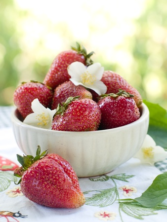 Fresh strawberries in ceramic bowl. Selective focus photo