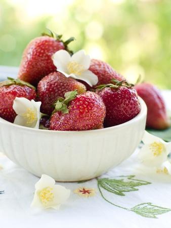 Fresh strawberries in ceramic bowl. Selective focus photo