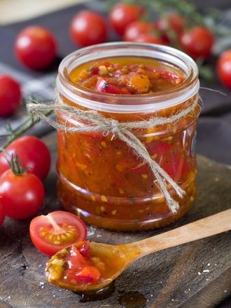 frutta sciroppata: Marmellata di pomodoro con pepe e aglio in un cucchiaio di legno. Messa a fuoco selettiva, rinunzia al superficiale