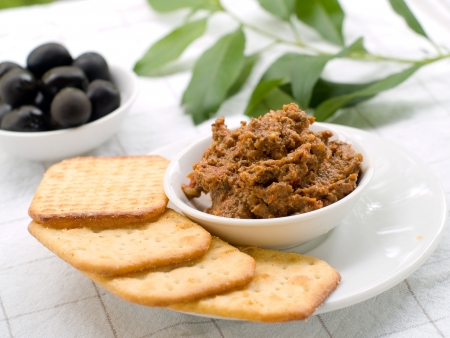 A small bowl of tapenade or olive paste with  crackers. Selective focus Stock Photo