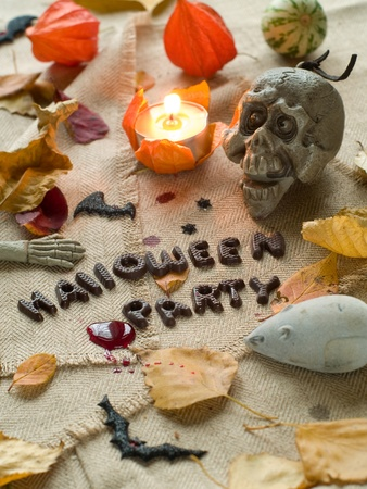 Halloween party text with autumn leaves, skull and mouse. Selective focus Stock Photo