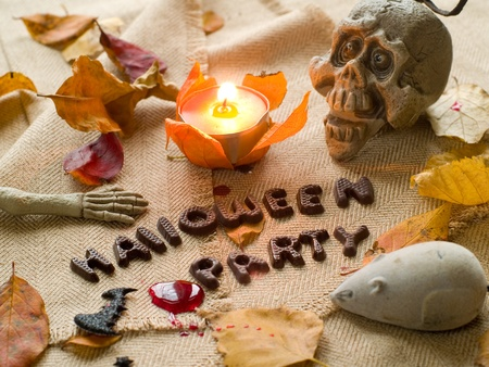 Halloween party text with autumn leaves, skull and mouse. Selective focus photo