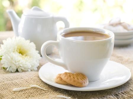 Frischer Kaffee mit Milch in Tasse mit Cookie hautnah. Selektiver Fokus