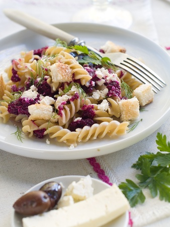 Fresh fusilli pasta with beet pesto and cheese. Selective focus photo