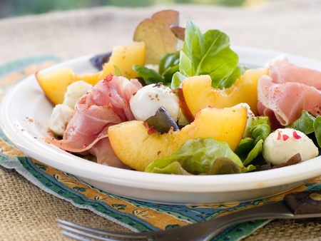 goat peach: Fresh salad with peach, mozzarella cheese and ham. Selective focus Stock Photo