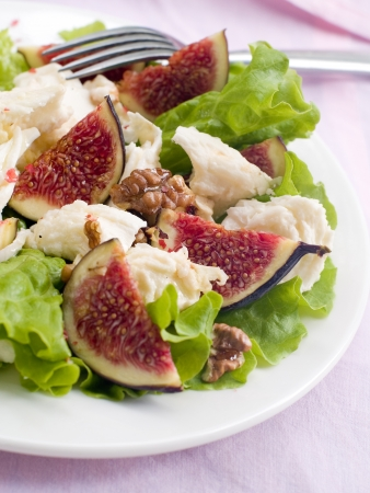 Figs salad with lettuce, cheese, walnut and honey. Selective focus photo