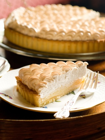 Slice of lemon merginue pie with cup of tea, selective focus Stock Photo