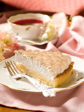 Slice of lemon merginue pie with cup of tea, selective focus photo