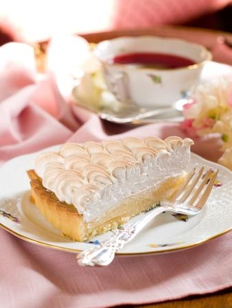 pie de limon: Rebanada de pastel de lim�n con merginue taza de t�, enfoque selectivo