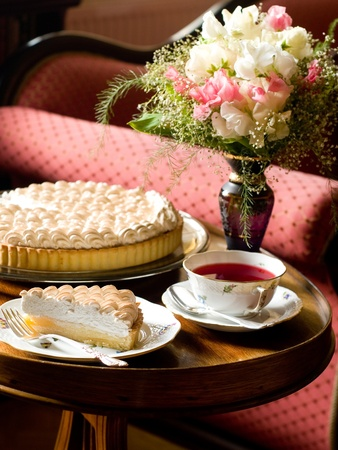 Lemon merginue pie  with cup of tea on table, selective focus photo