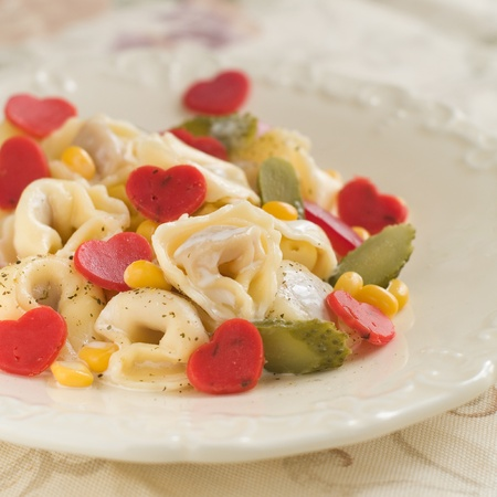 Tortellini with heart cheese and vegetable, selective focus photo