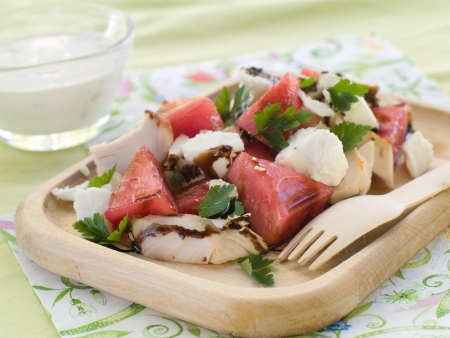 Summer salad from watermelon, chicken and feta on wooden plate, selective focus photo