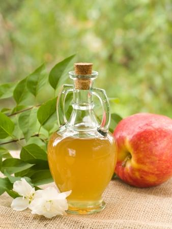 De vinagre de manzana en botella de vidrio, foco selectivo