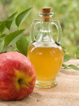 El vinagre de manzana en botella de vidrio, foco selectivo