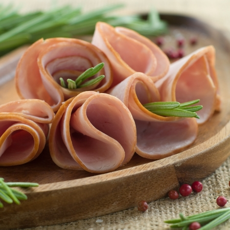 Delicious sliced ham on wooden plate with rosemary, selective focus Stock Photo