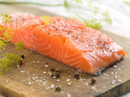 Fresh salmon fillet on wooden board, selective focus Stock Photo