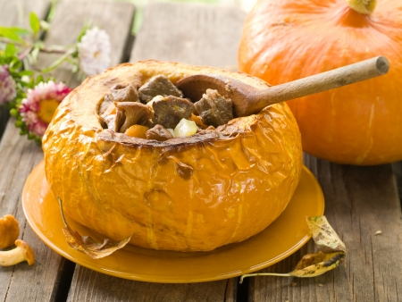 vegetable stew with meat in pumpkin on autumn decoration, selective focus