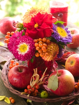 Composition with an autumn apples, flowers and rowan, selective focus photo