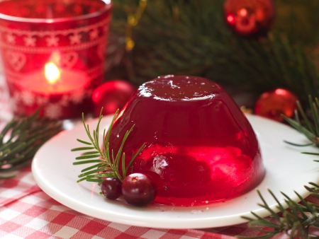 gelatin: A red berries jelly on a plate with christmas tree in the background, selective  focus