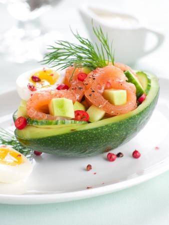 Salmon, avocado and egg salad in avocado, selective focus