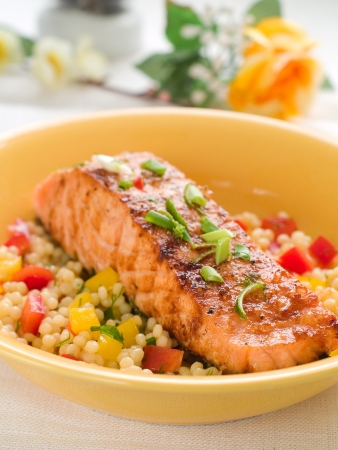 Grilled salmon with couscous  and vegetables, selective focus photo