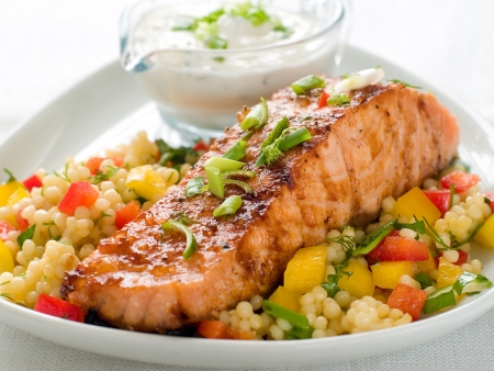 Grilled salmon with couscous  and sauce, selective focus photo