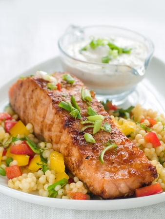 salmon dinner: Grilled salmon with couscous  and sauce, selective focus